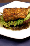 Sea bass dinner. Delicious grilled sea bass, seasoned with fine spices with asparagus and lettuce bed royalty free stock photos