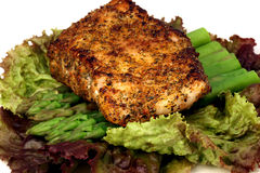 Sea bass dinner. Delicious grilled sea bass, seasoned with fine spices with asparagus and lettuce bed stock image