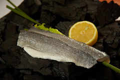 Sea bass fillet. A sea-bass fillet on coals ready for cooking with some herbs and a pies of lemon Stock Images