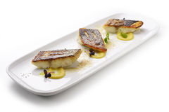 Sea bass fillet on persimmon sauce and powdered foie gras. Fish dish Sea bass fillet on persimmon sauce and powdered foie gras stock photo