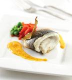 Sea bass fillet. On a plate with sauce, peppers and green peas royalty free stock photo