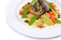 Sea bass fillet with spring vegetables and olive sauce Royalty Free Stock Photo