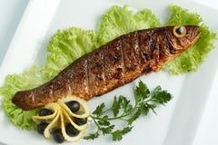 Sea bass on the grill. Lemon, lettuce, olives. White plate Stock Photo