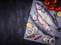 Sea bass with lemon, rosemary and spices on a black wooden table stock photo
