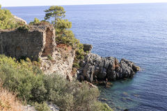 Sea bay with ancient ruins. Sea bay with remains of ancient city Iotape or Aytab with rocks and pine tress Stock Images