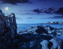 Sea bay with boulders and old city at night. Sea coast with giant boulders opposite to the old city on the other side of the bay at night in full moon light royalty free stock photography
