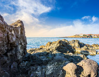 Sea bay with boulders and old city at sunrise Royalty Free Stock Photography