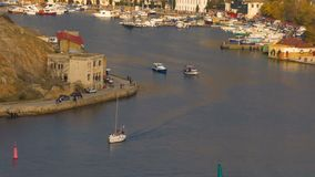 The sea bay of the city. Movement of motor boats along the bay. Movement of people on the city pier. City landscape of the bay the general plan stock video