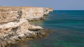 Sea bay of emerald color near coastal cliffs. Landscape of sea bay with rocky coast in sunny day stock footage