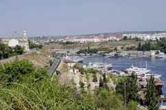 Sea bay with numerous yachts and boats at the berths. Sea bay in the city with the embankment and white ships off the coast stock photography