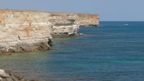 Sea bay of turquoise color near coastal cliffs. Sea bay of turquoise color near white coastal cliffs in sunny day stock footage