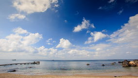 Sea Bay with Wooden Pier Rocks Waves Splash against Sky. Time-lapse of azure sea bay with wooden pier and rocks waves splash against blue sky white clouds stock footage