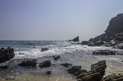 Sea beach on bay of Indian Ocean, Goa, India. Emerald waves of ocean under blue sky. Rocky coastline ends at sea shore and mountai stock images