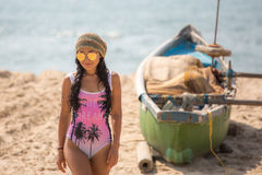 Sea, beach, boat and beautiful girl. Beautiful girl stands near a boat on the beach Stock Photography