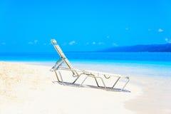 Sea beach chaise longue. White chaise lounge on the beach of the Caribbean sea wave stock photos
