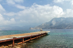 Sea beach coastline with wooden pier on Greek Royalty Free Stock Photo