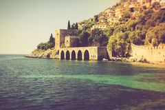 Sea beach in the morning. The old fortress and Mediterranean sea in Alanya, Turkey. Filtered image:cross processed vintage effect Royalty Free Stock Photography
