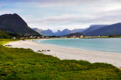 Sea beach in the mountains. Sandy sea beach in the mountains with grass in the foreground and coastal city in background. Blue sky wth clouds. Norway Stock Photos