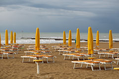 Sea beach on murky day. Photo closeup of sea beach with shut yellow sun umbrellas and orange chaise lounges standing in line on beige sand against cloudy sky Stock Images