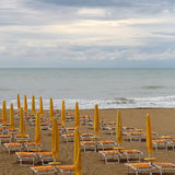 Sea beach on murky day. Photo closeup of sea beach with shut yellow sun umbrellas and orange chaise lounges standing in line on beige sand against cloudy sky Royalty Free Stock Photography