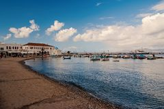 Sea beach in mykonos, greece. Church and houses in fishing village with nice architecture. Boats at sea port on blue sky. Summer vacation on mediterranean stock image