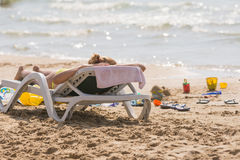 On sea beach near the water with a beach chair sunbathing girl, spanking and childrens sand toys Royalty Free Stock Photography