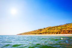 Sea beach with rock and clay coast, sunny hot Stock Images