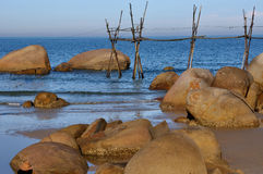 Sea beach with rock and wooden shelf. Sea beach coast with rocks and shelf in morning light Royalty Free Stock Photo