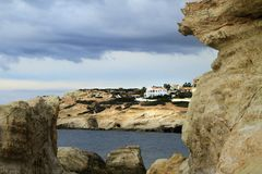 Sea beach rockssea beach rocks sun clouds homes stone breakage Cyprus blue calm sun clouds homes stone cliff Royalty Free Stock Images