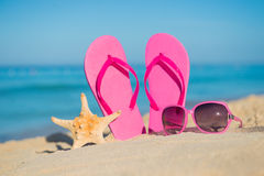 The sea, beach, sand and women's accessories: pink flip-flops, sunglasses and starfish Stock Photography