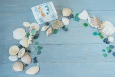 Sea, beach saver, background, postcard. the mood of rest, vacation. Shells of stone pebbles and a white chest on a gentle light blue wooden background Royalty Free Stock Image