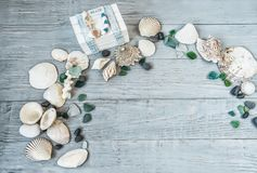 Sea, beach saver, background, postcard. the mood of rest, vacation. Shells of stone pebbles and a white chest on a gentle light blue vintage, gray, old, wooden Royalty Free Stock Photography