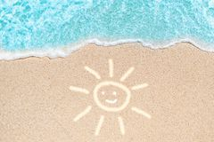 Sea Beach and Soft wave of blue ocean. Summer day and sandy beach background with painted smiling sun as shape lines on sand. stock image