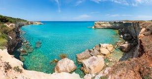 Sea beach Spiaggia della Punticeddha, Salento, Italy. Picturesque seascape with white rocky cliffs, sea bay, islets and faraglioni at beach Spiaggia della royalty free stock image