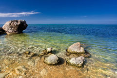 Sea beach with stones. In blue water Stock Image