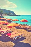 Sea beach - Tenerife. Vacant umbrellas and chaise longues on a sea beach, Tenerife. Retro style filtered image royalty free stock image