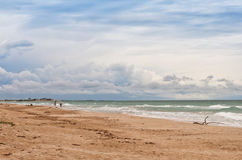 The sea beach. Two persons walk on the sand beach Royalty Free Stock Image