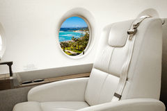 Sea and beach view in aircraft window, business jet flight Stock Image