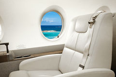 Sea and beach view in aircraft window, business jet flight Stock Images