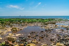 Sea and beach view in Ramsgate, Kent UK. View of beach and sea at low tide with stones covered in seaweed in Ramsgate, Kent, UK Stock Photography