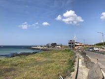Sea beach with windmill in Jeju Island Korea. Blue sky and nice Sea beach with windmill in Jeju Island Korea royalty free stock photo