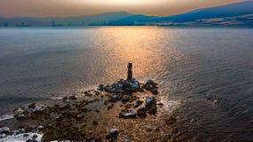 Sea beacon on stones. Sea beacon in the winter stock photography