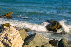 Sea, big wave and splashes over the stones Stock Photos