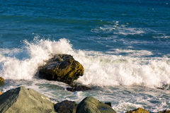 Sea, big wave and splashes over the stones Stock Image