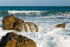 Sea, big wave and splashes over the stones Stock Images