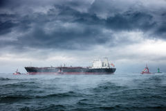 Sea in a blizzard. Dark image of tanker and tugboats on sea during a violent blizzard royalty free stock photo