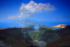 Sea, blue sky and crater. Blue sky, clouds,  and crater with yellow sulphur on the sides. Vulcano island in Italy Stock Images