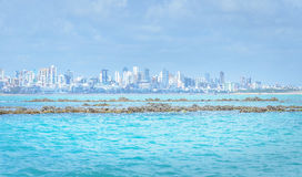 Sea with blue water with some rocks and background city. Royalty Free Stock Image