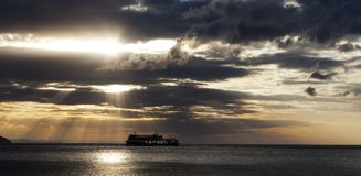 Sea with sea boat and gray sky with sun at sunset Royalty Free Stock Photography
