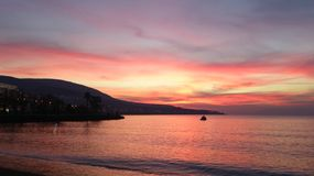 Sea with boat in sunset time. Beautiful bright pink sunset in Dikili, Izmir, Turkey. Horizontal landscape with seaside and cloudy sky Stock Photography